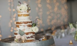 Naked wedding cake with roses on a rustic barrel