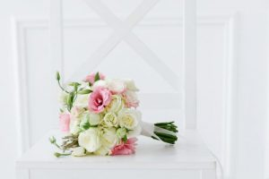 wedding bouquet on white chair with ribbon