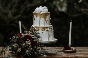 White and gold wedding drip cake with red rose bouquet