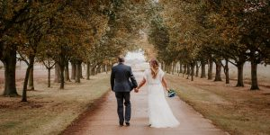 Bride and groom walking hand in hand down tree lined path
