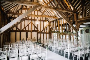 wedding ceremony within barn with exposed beams | Essex Wedding Planner