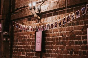 String of polaroid photos against exposed brick wall at a Essex wedding