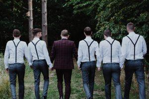 Groom & Groomsmen in braces walking together at wedding