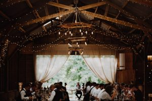 Guests eating wedding breakfast in an Essex Dry Hire wedding barn with fairy light canopy