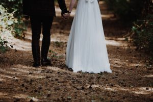Bride and Groom hand in hand through woodland