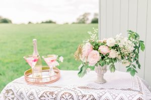 Lace Tablecloth with urn of flowers and two pink cocktails | Essex Wedding Planner