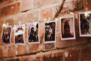 Polaroid photos at a wedding against an exposed brick wall