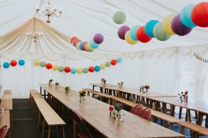 Relaxed marquee set up for wedding with wooden benches and coloured lanterns