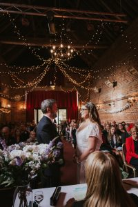 Bride and groom exchanging their wedding vows with fairy lights