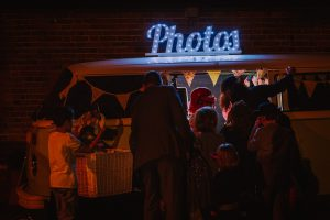 Wedding guests enjoying a photo booth within a VW camper van