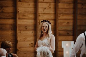 Bride giving her speech with red rose flower crown and lace detailed dress