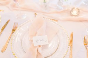 Bride place setting with pink napkin and gold beaded charger plate | Essex Wedding Planner