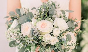 Brides wedding day bouquet with white and blush roses with lots of foilage