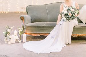 Bride sitting on velvet chair holding cascading silk ribbon from bridal bouquet