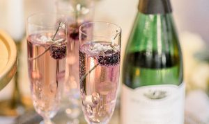 Champagne in flute with blackberries and edible flowers