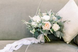 Wedding bouquet on velvet sofa with cascading silk ribbon