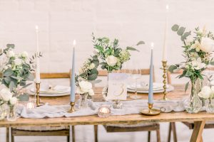 Bud vase, silk table runner, brass candlesticks with blue and while tapered candles on wedding top table