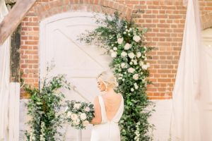 Bride standing in front or a deconstructed white & green floral arch