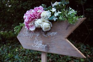 Happily Ever After wedding sign with white and purple flowers