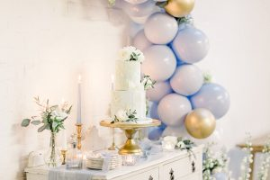 Blue and gold balloon garland and elegant cake table at your wedding