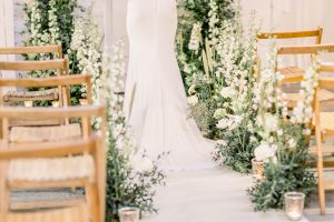 Bride standing at aisle surrounded by white & green flowers and wooden seats | Essex wedding planner