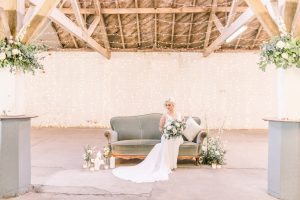 Bride on velvet sofa with flowers and candles / Essex wedding Planner