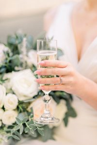 Bride holding a flute of champagne wearing engagement ring / Essex wedding planner
