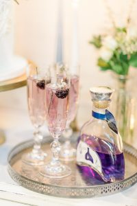 Champagne flutes with a delicate purple gin bottle on a silver tray   Essex Wedding Planner