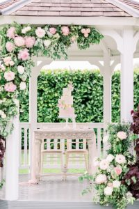 Pink & white three tiered wedding cake on table framed with flowers | Essex Wedding Planner