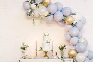 Blue wedding cake on gold cake stand with blue & gold balloon garland | Essex Wedding Planner
