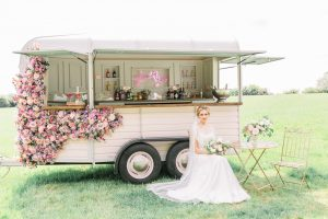 Bride on a chair in front of a converted horse box bar | Essex Wedding Planner