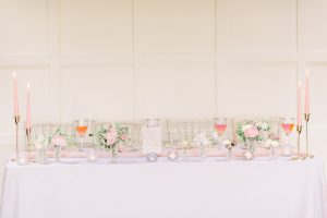 Pink wedding table with tapered candles and bud vases | Essex Wedding Planner